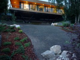 Jednopodlažní rodinný dům vznášející se nad prudkým svahem a vyhlížející na město Mšeno